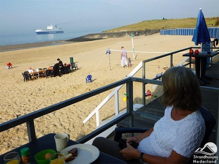 Grote schepen varen vlakbij strandhuisjes Vlissingen