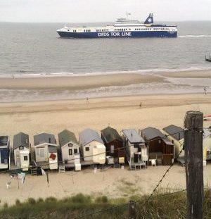 Zeeschip bij strandhuisjes Dishoek